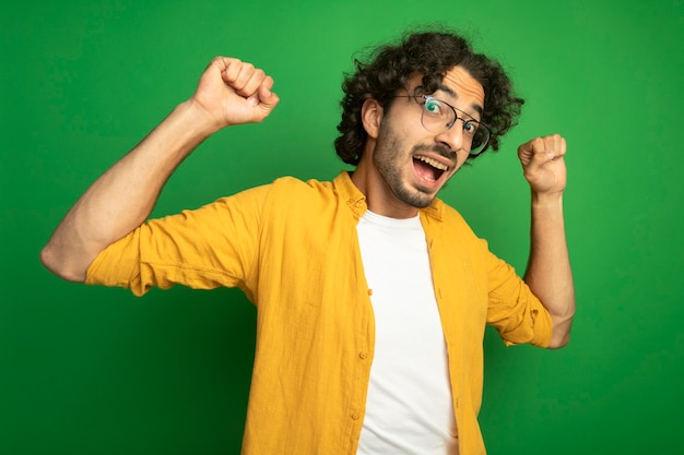 Vrolijke jonge knappe blanke man met bril vuisten omhoog geïsoleerd op groene muur