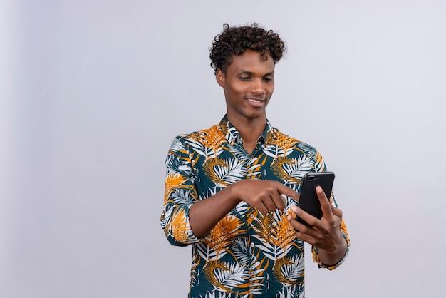Vrolijke jonge knappe donkerhuidige man met krullend haar in bladeren gedrukte shirt smartphone hand in hand en scherm van mobiele telefoon aan te raken op een witte achtergrond