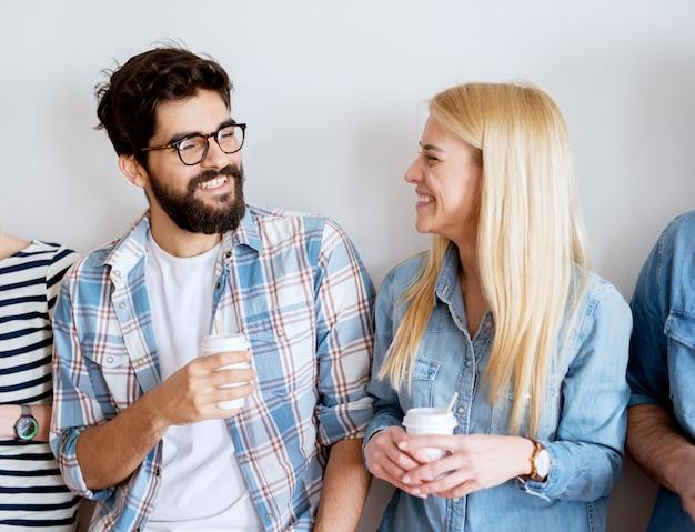 Vrolijke jonge knappe glimlachende collega paar plezier op een pauze van het werk en koffie drinken in een papieren beker tegen de muur leunend.