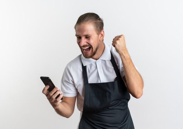Vrolijke jonge knappe kapper die eenvormig bedrijf draagt en mobiele telefoon bekijkt en vuist opheft die op wit wordt geïsoleerd