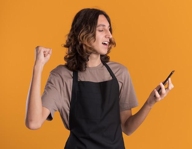Vrolijke jonge knappe kapper die uniform vasthoudt en naar een mobiele telefoon kijkt die ja gebaar doet