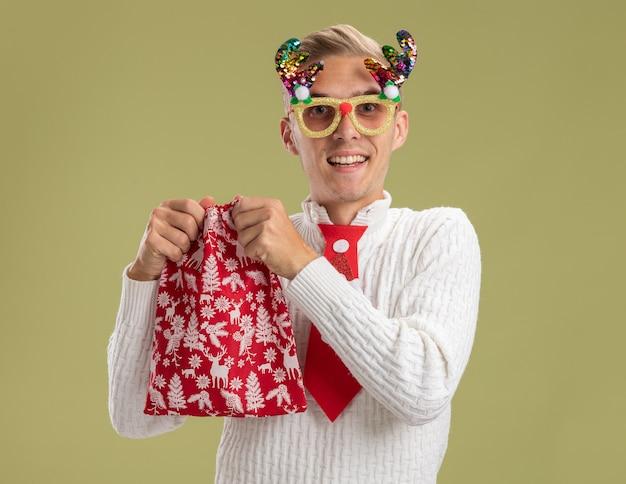 Vrolijke jonge knappe kerel die de bril van de kerstmisnieuwigheid draagt die kerstmiszak houdt die zich klaar maakt om het te openen geïsoleerd op olijfgroene muur