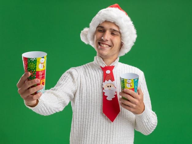 Vrolijke jonge knappe kerel die kerstmuts en stropdas van de kerstman draagt ?? die plastic kerstbekers vasthoudt en uitrekt en kijkt naar een van hen geïsoleerd op groene muur