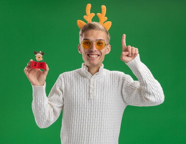 Vrolijke jonge knappe kerel dragen rendieren gewei hoofdband met bril kerstboom speelgoed met datum kijken camera omhoog geïsoleerd op groene achtergrond kijken
