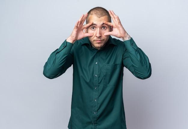 Vrolijke jonge knappe kerel met een groen shirt die handen rond de ogen legt