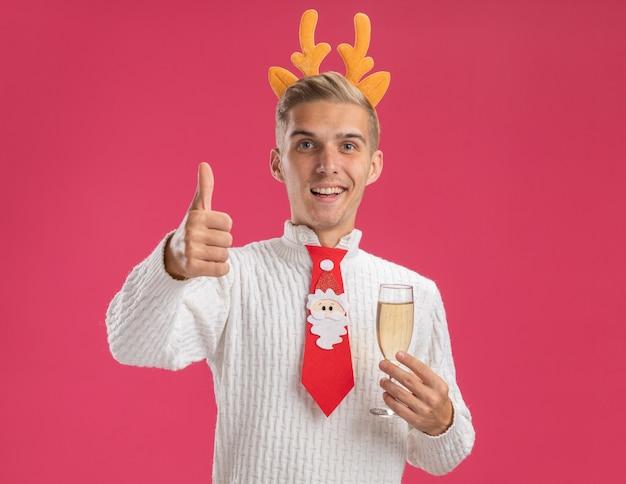 Vrolijke jonge knappe kerel met rendiergeweien hoofdband en stropdas van de kerstman bedrijf glas champagne kijken camera weergegeven: duim omhoog geïsoleerd op roze achtergrond