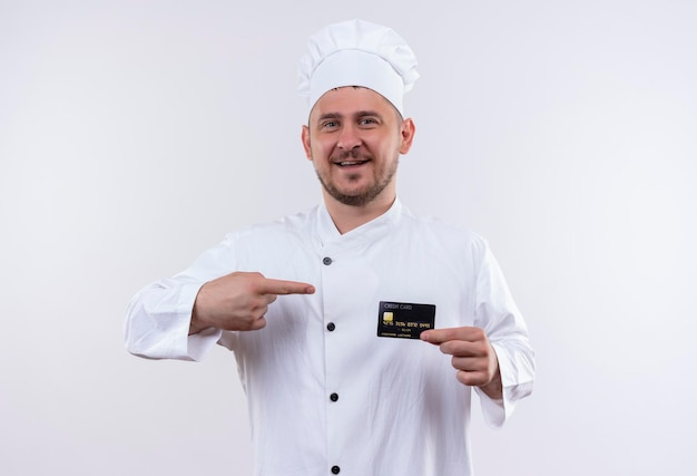 Vrolijke jonge knappe kok in chef-kok uniform houden en wijzend op creditcard geïsoleerd op een witte muur