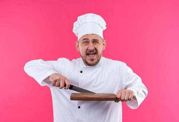 Vrolijke jonge knappe kok in uniform van de chef-kok met mes en snijplank geïsoleerd op roze muur
