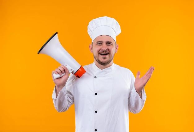 Vrolijke jonge knappe kok in uniform van de chef-kok met spreker geïsoleerd op oranje muur