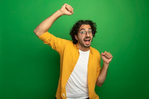 Vrolijke jonge knappe man die een bril draagt die en vuist opheft die omhoog kijkt die voorzijde op groene muur wordt geïsoleerd