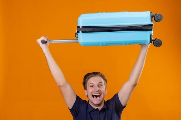 Vrolijke jonge knappe reizigersmens die zich met koffer boven zijn hoofd bevinden opgewekt en gelukkig over oranje achtergrond
