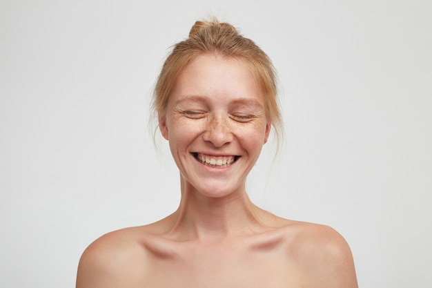 Vrolijke jonge knappe roodharige dame met knot kapsel lachen gelukkig met gesloten ogen, toont haar aangename emoties terwijl poseren op witte achtergrond