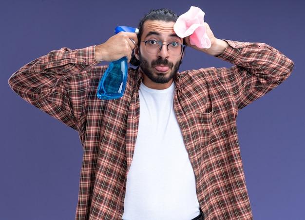 Vrolijke jonge knappe schoonmaakster die de spuitfles van de t-shirtholding met lap rond gezicht draagt die tong toont die op blauwe muur wordt geïsoleerd