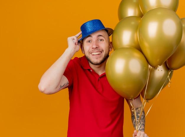 Vrolijke jonge knappe slavische partijkerel die partijhoed draagt ?? die ballons houdt die camera bekijkt die hoed bekijkt die op oranje achtergrond wordt geïsoleerd
