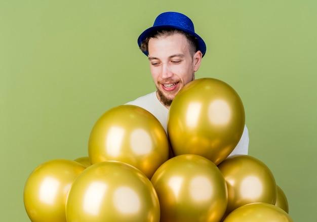 Vrolijke jonge knappe slavische partijkerel die partijhoed draagt die zich achter ballons bevindt en hen bekijkt geïsoleerd op olijfgroene achtergrond