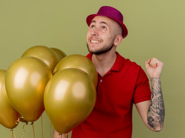 Vrolijke jonge knappe slavische partijkerel die partijhoed draagt die zich dichtbij ballons bevindt die omhoog doen ja gebaar geïsoleerd op olijfgroene achtergrond kijken