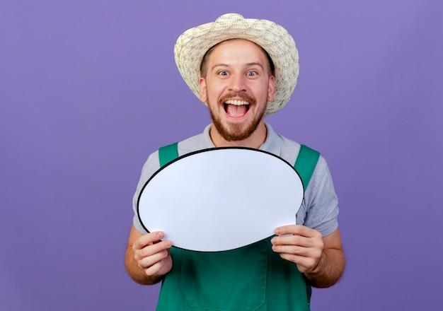 Vrolijke jonge knappe slavische tuinman in uniform en hoed met praatjebel geïsoleerd op zoek