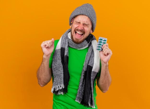 Vrolijke jonge knappe slavische zieke man met muts en sjaal, pak capsules, ja gebaar met gesloten ogen te houden