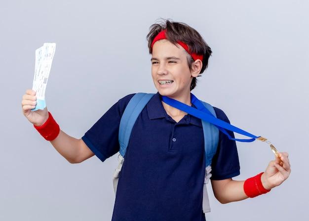 Vrolijke jonge knappe sportieve jongen hoofdband en polsbandjes en medaille dragen rond nek terug tas met beugels kijken kant bedrijf vliegtuigtickets en medaille geïsoleerd op witte achtergrond