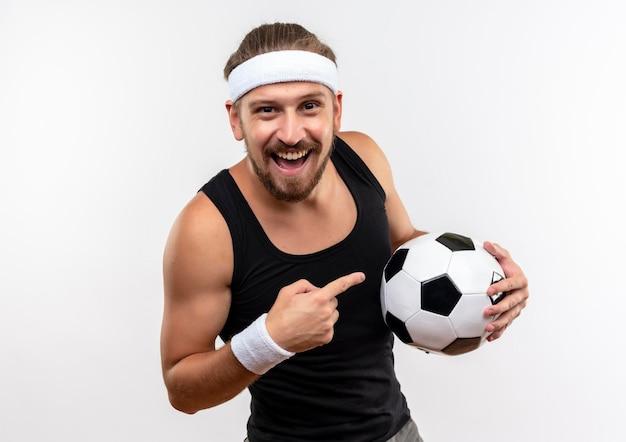 Vrolijke jonge knappe sportieve man met een hoofdband en polsbandjes die de voetbal op een witte muur houden en wijzen