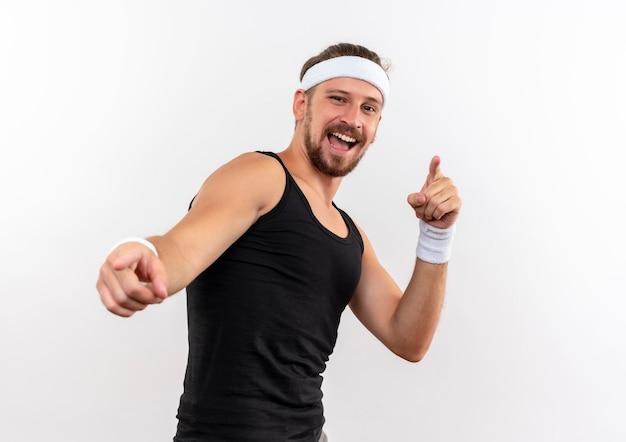 Vrolijke jonge knappe sportieve man met hoofdband en polsbandjes die je gebaar doen geïsoleerd op een witte muur