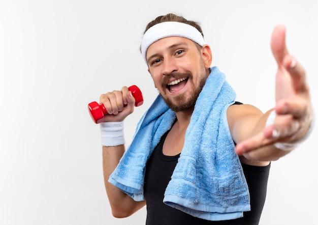 Vrolijke jonge knappe sportieve man met hoofdband en polsbandjes met halter en hand uitstrekkend naar met handdoek om nek geïsoleerd op witte muur