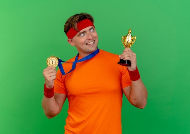 Vrolijke jonge knappe sportieve man met hoofdband en polsbandjes met medaille rond nek met medaille en winnaar beker kijken naar beker geïsoleerd op groen