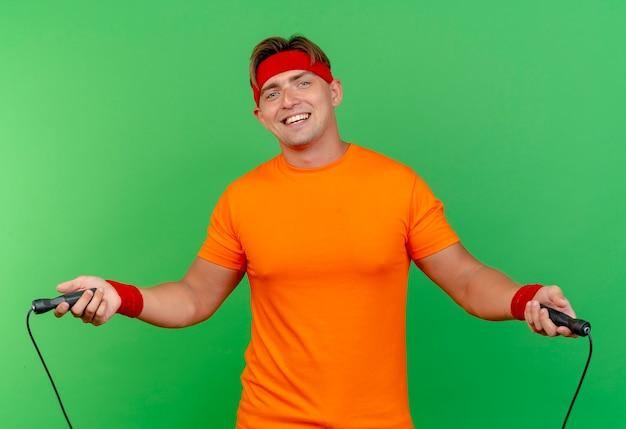 Vrolijke jonge knappe sportieve man met hoofdband en polsbandjes touwtjespringen geïsoleerd op groen