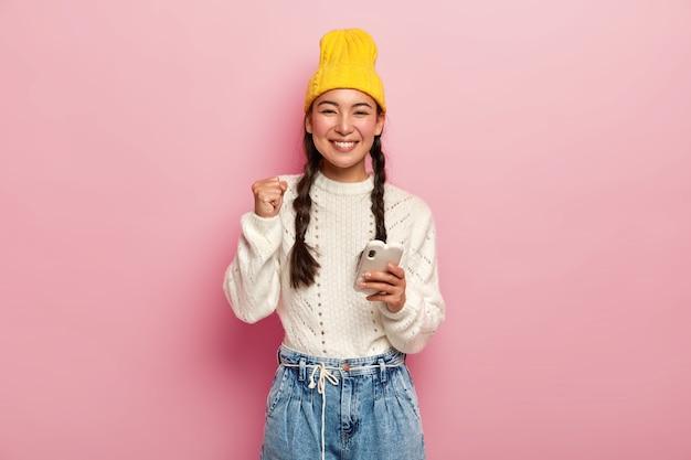 Vrolijke jonge koreaanse vrouw balt vuist, draagt gele stijlvolle hoed en witte trui, glimlacht aangenaam, houdt moderne mobiele telefoon, geïsoleerd over roze studiomuur