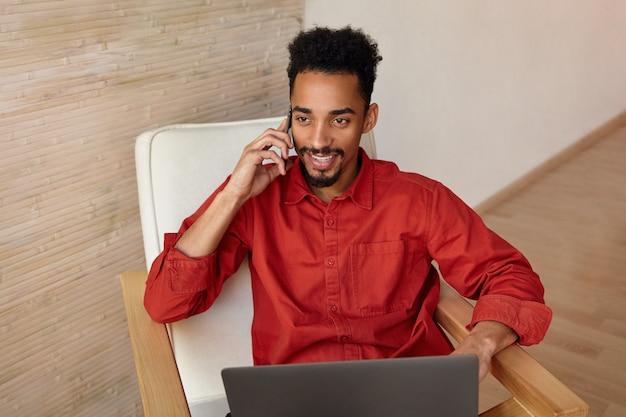 Vrolijke jonge kortharige donkerhuidige brunette man gekleed in een rood shirt lacht graag terwijl het hebben van een aangenaam telefoongesprek, zittend op het interieur