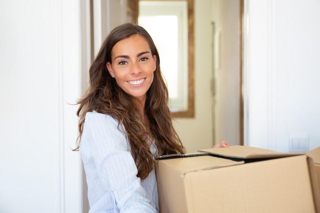 Vrolijke jonge latijnse vrouw die naar een nieuw appartement verhuist, kartonnen doos vasthoudt en draagt,