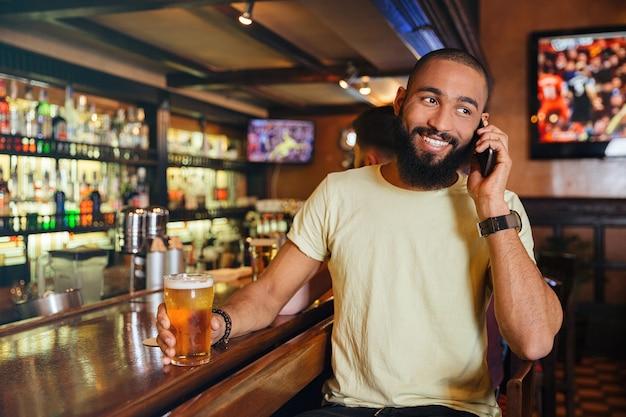 Vrolijke jonge man bier drinken en praten op mobiele telefoon in pub