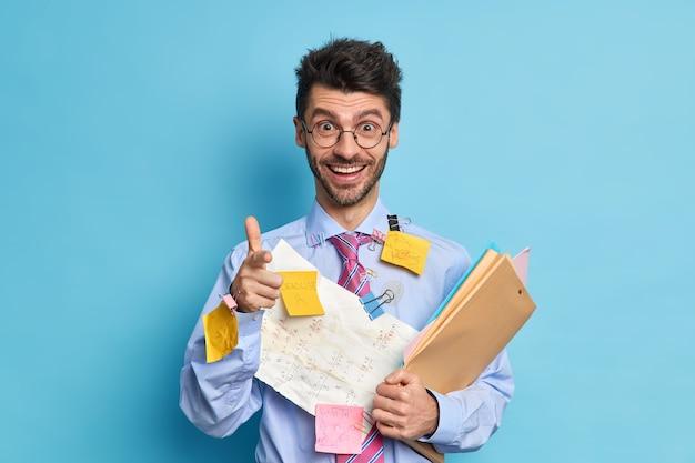 Vrolijke jonge man collega blij om projectwerk bedekt met papieren en stickers af te ronden wijst naar je vinger pistool gebaar maakt. succesvolle ijverige student bezig met cursuswerk vormt binnen