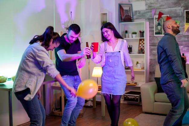 Vrolijke jonge man die een bierflesje vasthoudt terwijl hij danst met zijn vrienden op een feestje met discomuziek en ballonnen.
