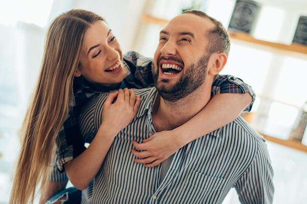Vrolijke jonge man die een lachende vrouw op zijn rug draagt