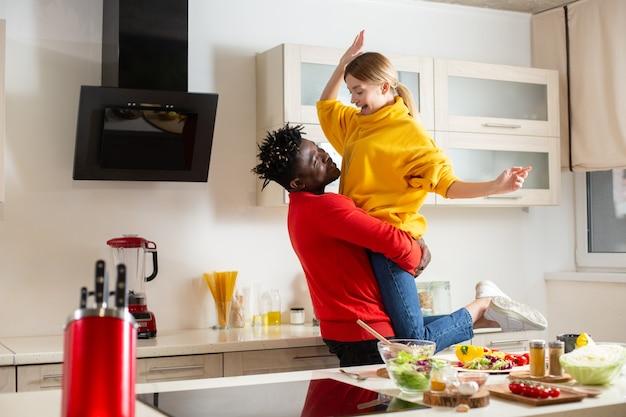 Vrolijke jonge man die in de keuken staat en glimlacht terwijl hij zijn gelukkige vriendin in de lucht steekt