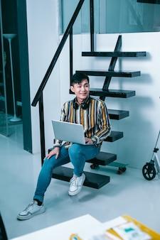 Vrolijke jonge man die in een modern kantoor werkt en glimlacht terwijl hij met een laptop op de trap zit