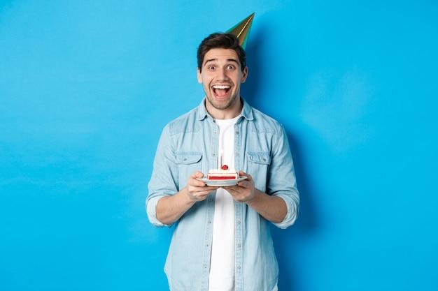 Vrolijke jonge man die verjaardag viert in feestmuts, verjaardagstaart vasthoudt, staande tegen een blauwe achtergrond