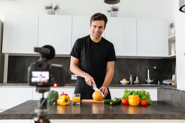 Vrolijke jonge man die zijn video-blog-aflevering filmt