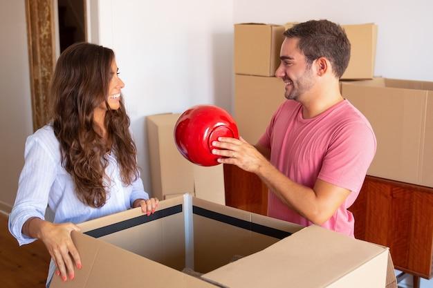Vrolijke jonge man en vrouw die dingen verplaatsen en uitpakken, voorwerp van open kartondoos uitstappen