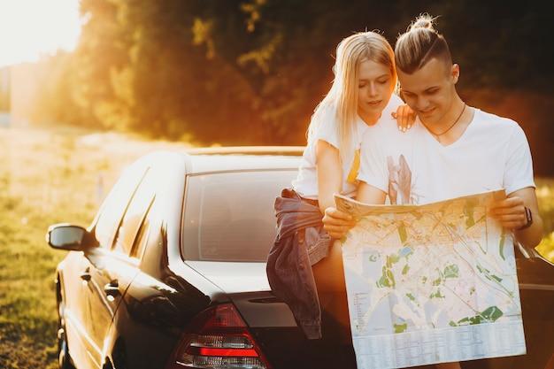 Vrolijke jonge man en vrouw die op kofferbak van auto in aard leunen en kaart lezen