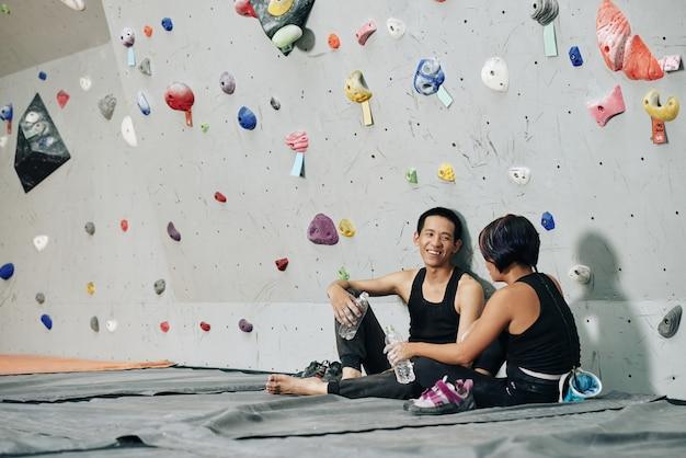 Vrolijke jonge man en vrouw die zoet water drinken en praten tijdens het rusten na het klimmen in het bouldercentrum