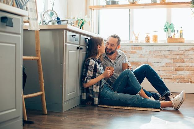 Vrolijke jonge man en vrouw genieten van ochtendthee in de keuken en glimlachen naar elkaar
