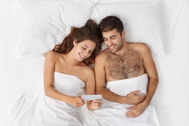 Vrolijke jonge man en vrouw ontspannen in bed voor het slapen gaan en kijken naar het scherm van de mobiele telefoon