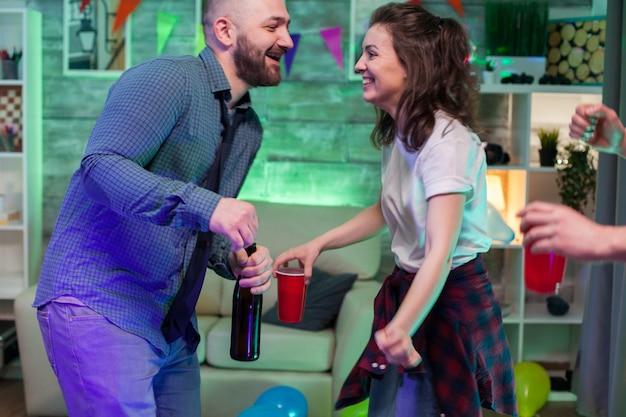 Vrolijke jonge man en vrouw op een feestje dansen. man met een bierflesje.