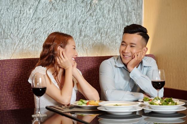 Vrolijke jonge man en vrouw zitten aan de tafel van het restaurant met smakelijke gerechten en kijken naar elkaar