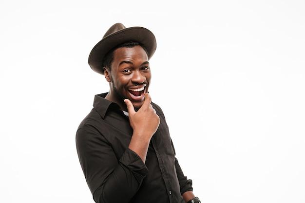 Vrolijke jonge man gekleed in overhemd met hoed