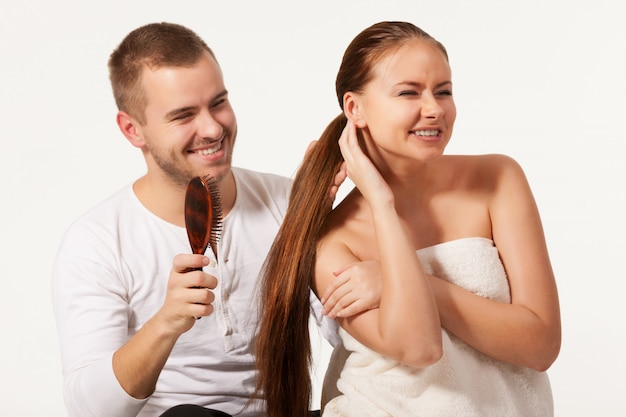 Vrolijke jonge man haren dame borstelen.