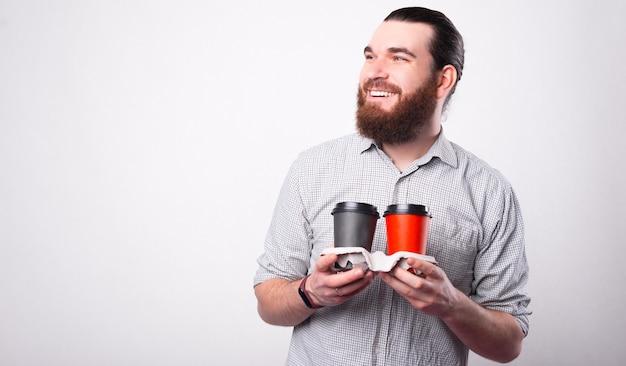 Vrolijke jonge man houdt twee warme dranken in papper cups glimlachend kijkt weg in de buurt van een witte muur