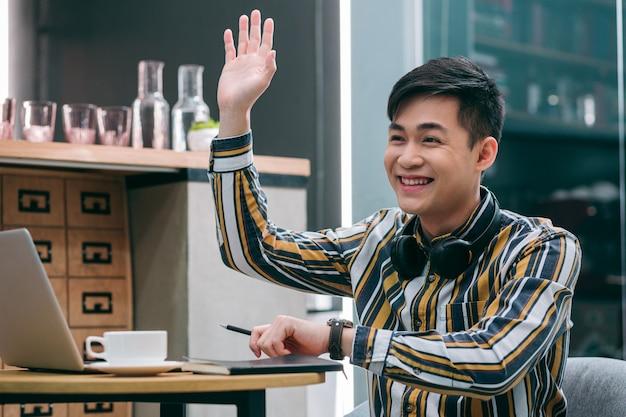 Vrolijke jonge man in een café die één hand opsteekt terwijl hij naar iemand in de verte zwaait